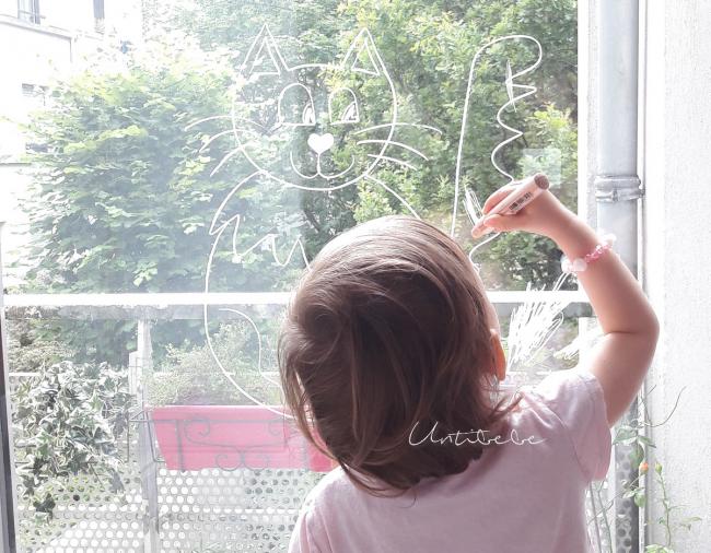enfant dessine sur vitres